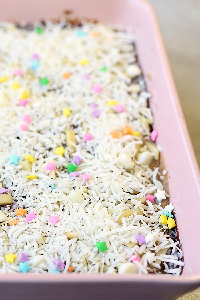 Spring just got sweeter with these easy Magic Layer Brownie Bars made with 3-ingredient Paleo brownies, coconut milk chocolate ganache, date caramel, almond slivers, white chocolate chips and toasted coconut! #tollhouse #SpringJustGotSweeter #Ad #magic #layer #brownies #glutenfree #desserts #sweets #treats | Delightfulmomfood.com