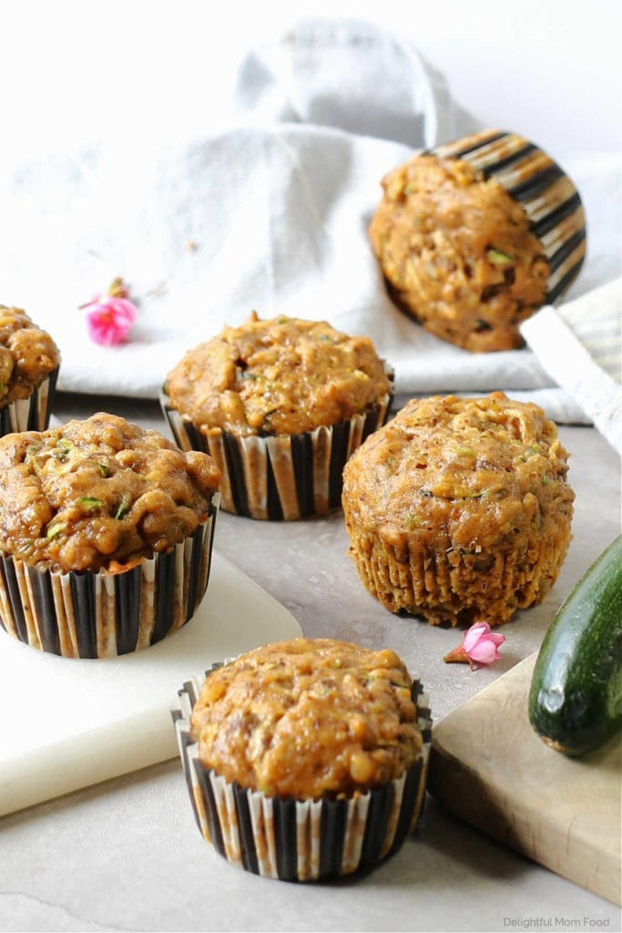 gluten free zucchini pumpkin muffins surrounded by cutting boards pink flower and fresh zucchini