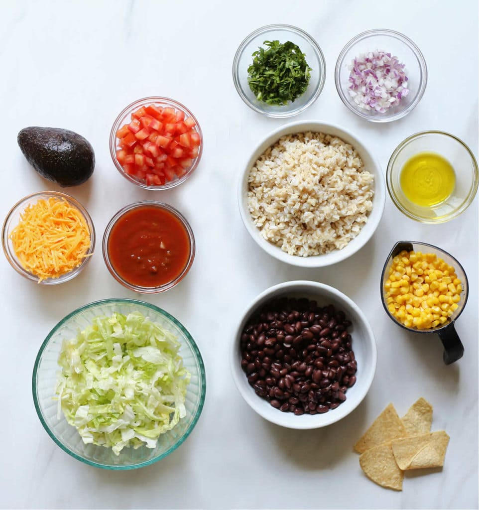 vegetarian taco salad ingredients in bowls: black beans, rice, salsa, tomatoes, lettuce, cilantro, onion, chips