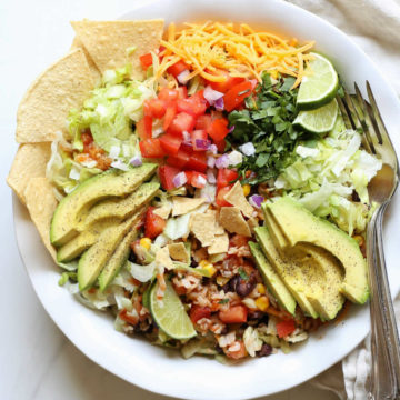 Black bean taco salad in a bowl with avocado slices and tortilla chips