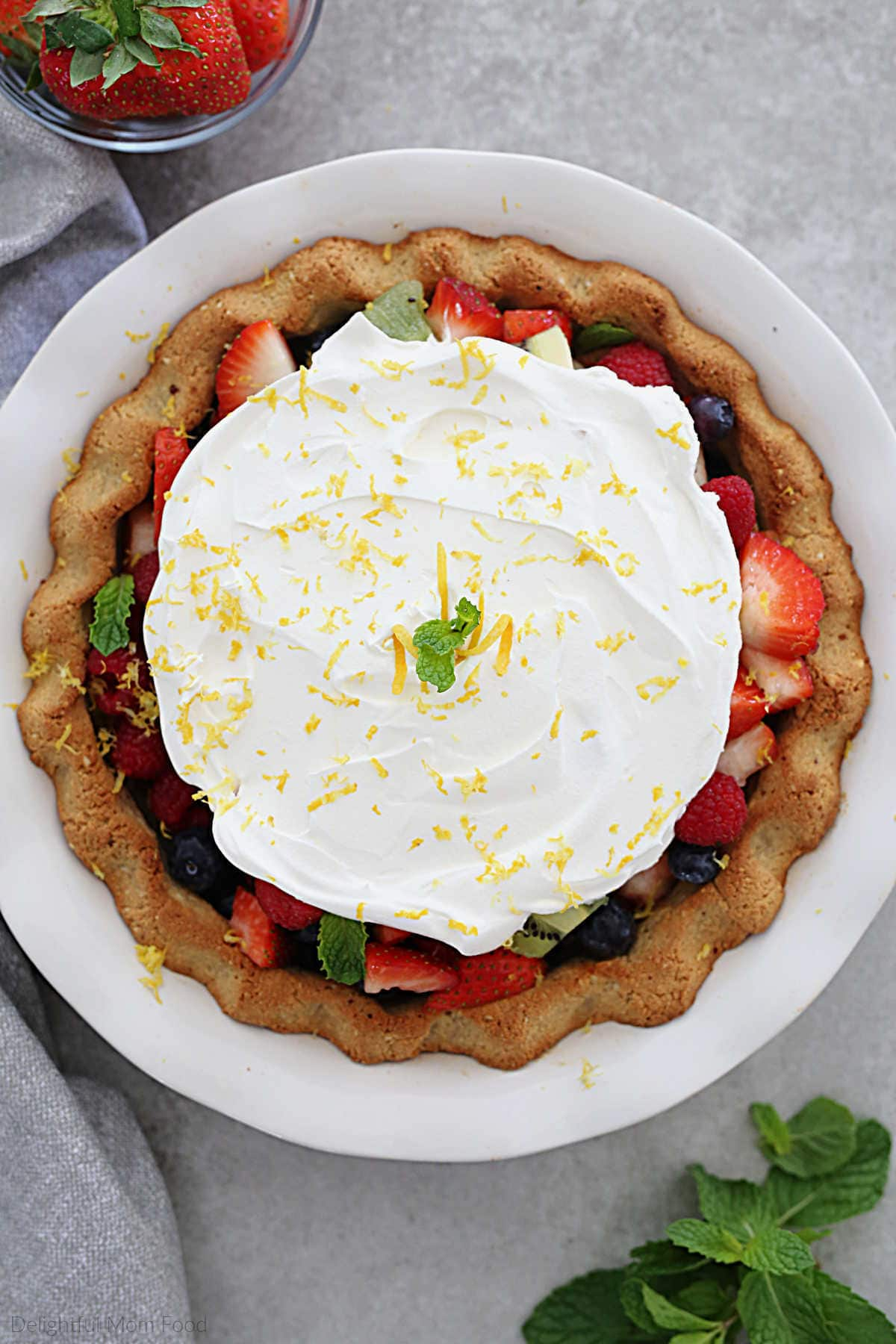 paleo pie crust filled with fresh fruit and topped with whipped cream dairy-free topping