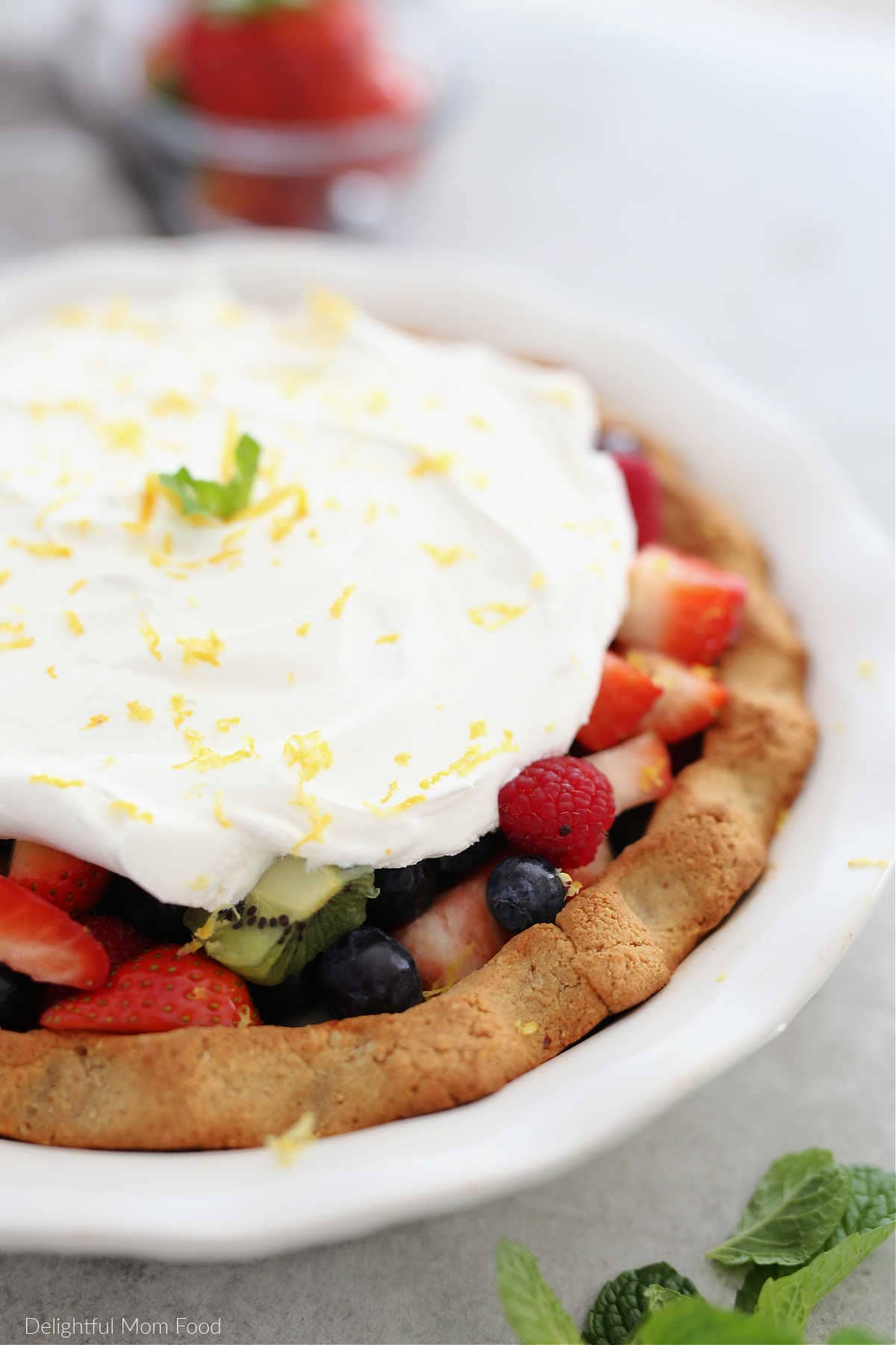 paleo pie crust filled with fresh fruit and a whipped topping