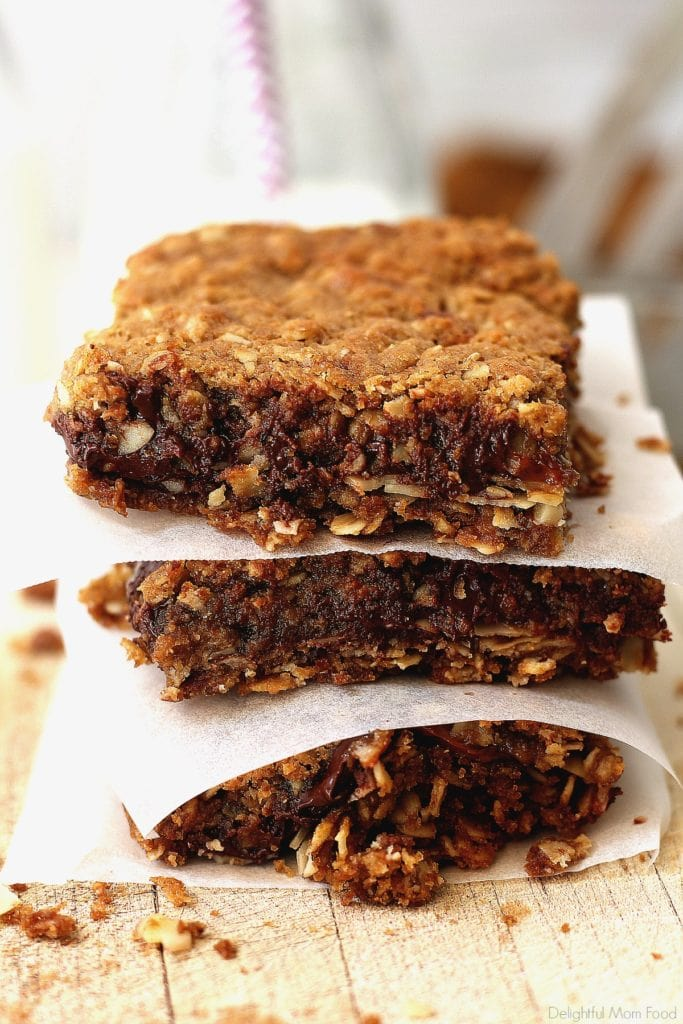 Caramel Chocolate Oat Bars stacked with wax paper between each square