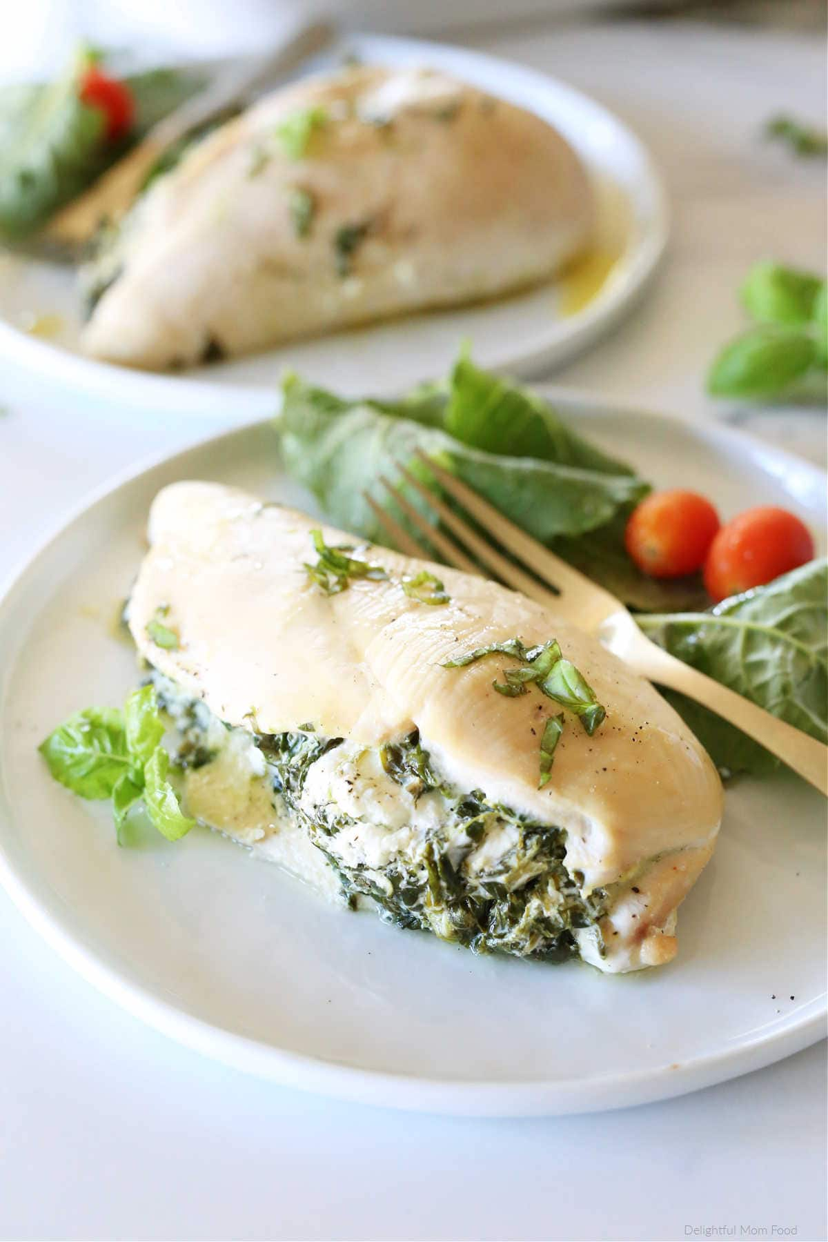 Stuffed Chicken filled with spinach and goat cheese on a white plate