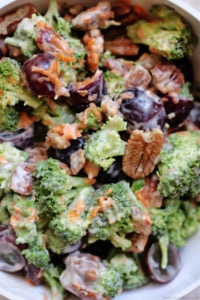 broccoli and grape salad with pecans and shredded carrots tossed in creamy dressing in a bowl
