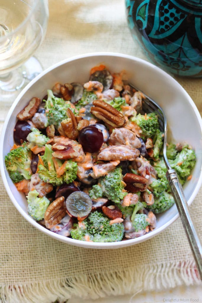 broccoli salad with grapes, pecans, carrots and a creamy dressing in a bowl with a fork