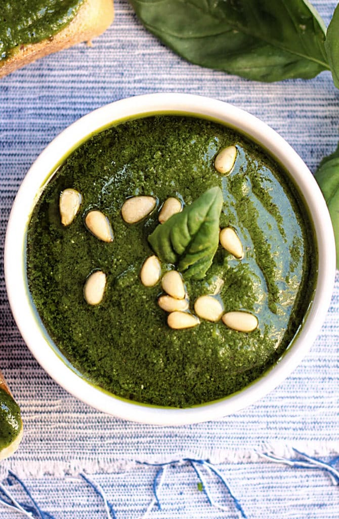 kale pesto sauce made with basil leaves served in a bowl with pine nuts on top