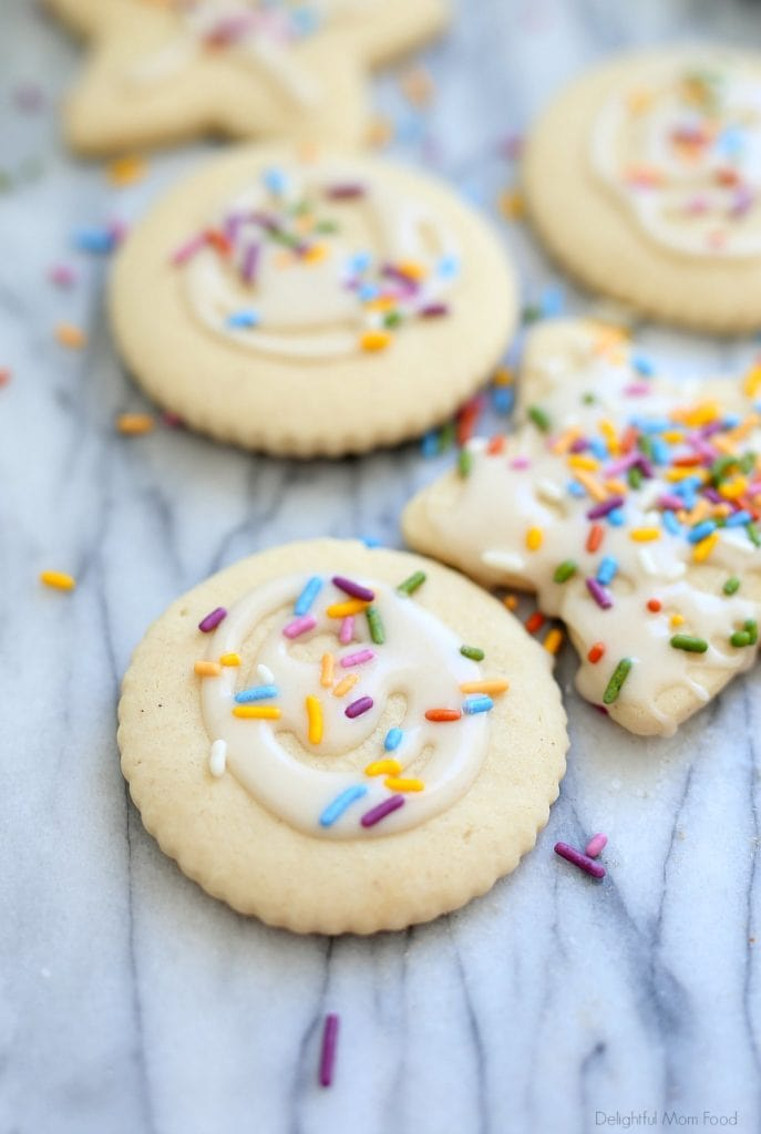 cut out gluten free sugar cookies decorated with white icing and rainbow sprinkles