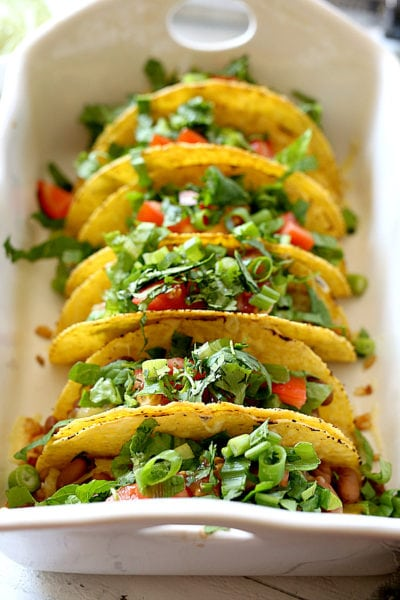 Mexican rice, beans, cheese, lettuce, cilantro and tomatoes stuffed into hard shell tacos and topped with a creamy green vegan sauce. Super easy and healthy recipe for hard shell tacos in under 30 minutes