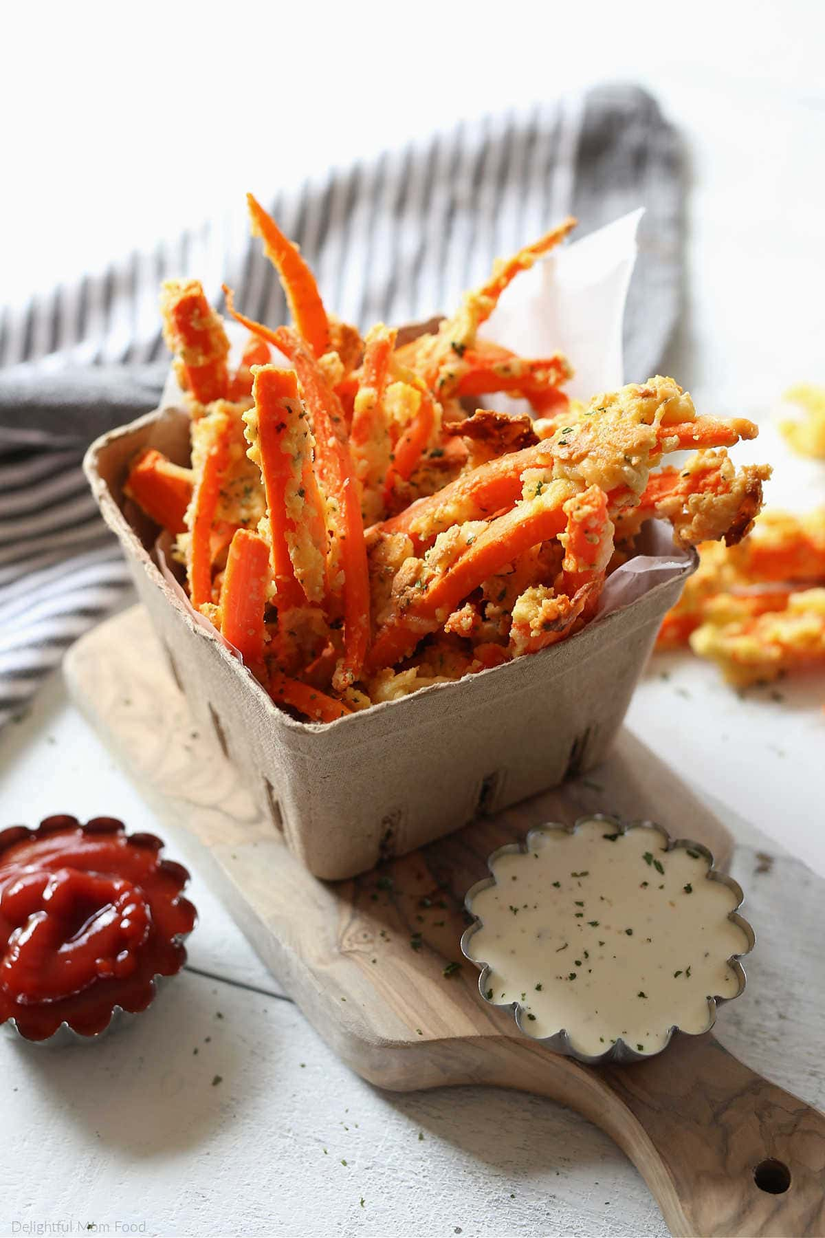 Carrot Fries in a cardboard cup on a cutting board served with ketchup and dressing