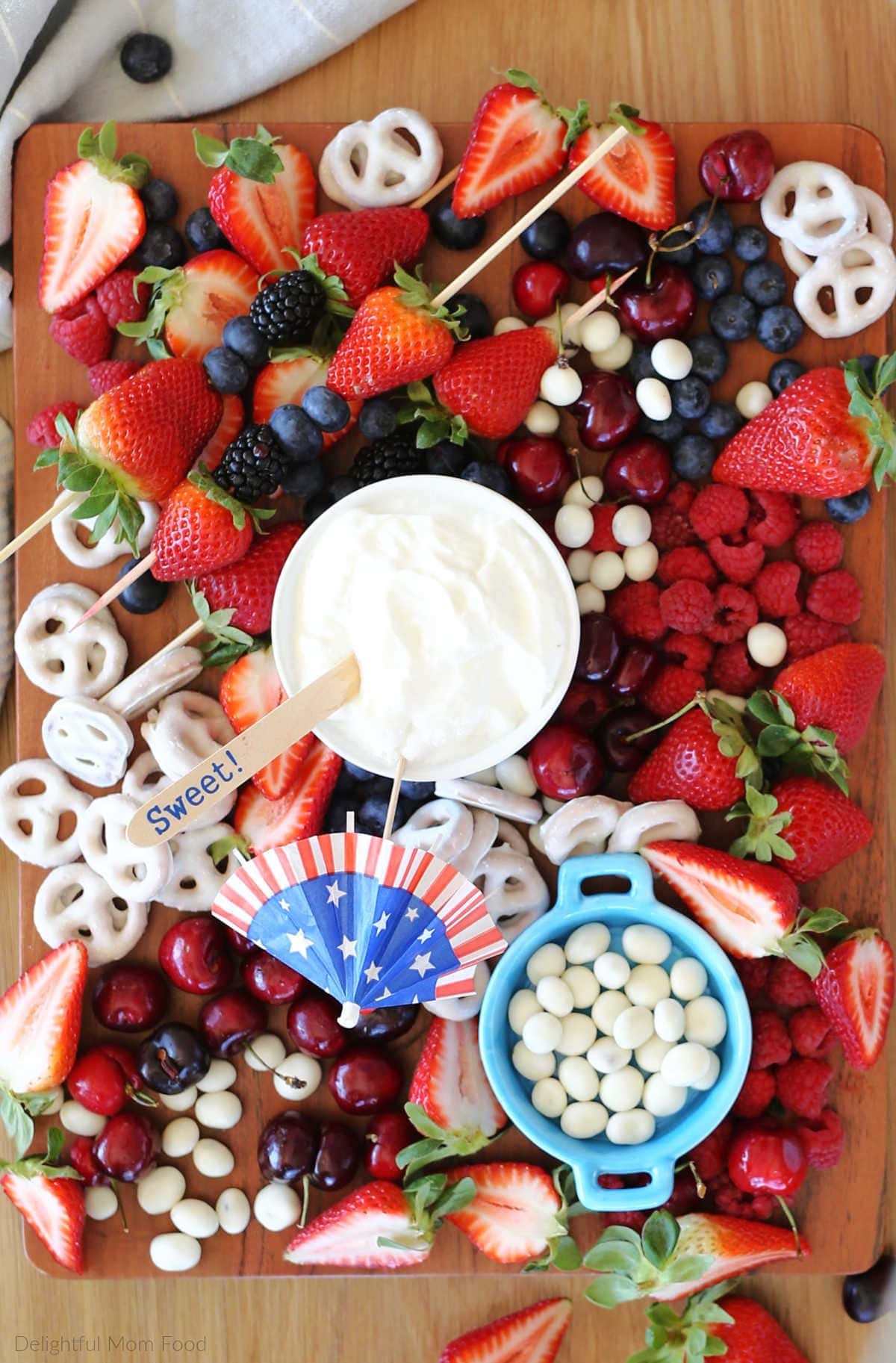 wood platter topped with strawberries cherries blueberries yogurt pretzels and yogurt dip for a simple red white blue theme for 4th of july