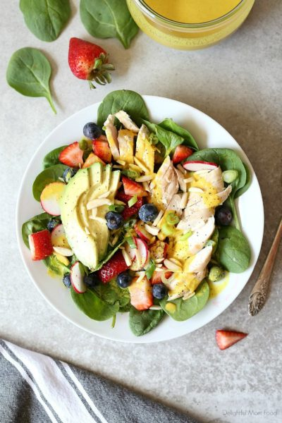 Super charge your day with this easy grilled chicken spinach salad topped with strawberries, blueberries, almonds, avocado and an anti-inflammatory turmeric almond salad dressing! #salad #spinachsaladrecipe #spinach #strawberries #blueberries #almonds #healthy #grilledchicken #maindish #healthy #dressing #turmeric | Recipe at delightfulmomfood.com