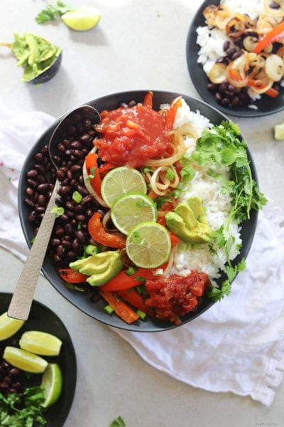 black bean vegetarian burrito bowl topped with avocado salsa cilantro and limes on a plate with a serving spoon