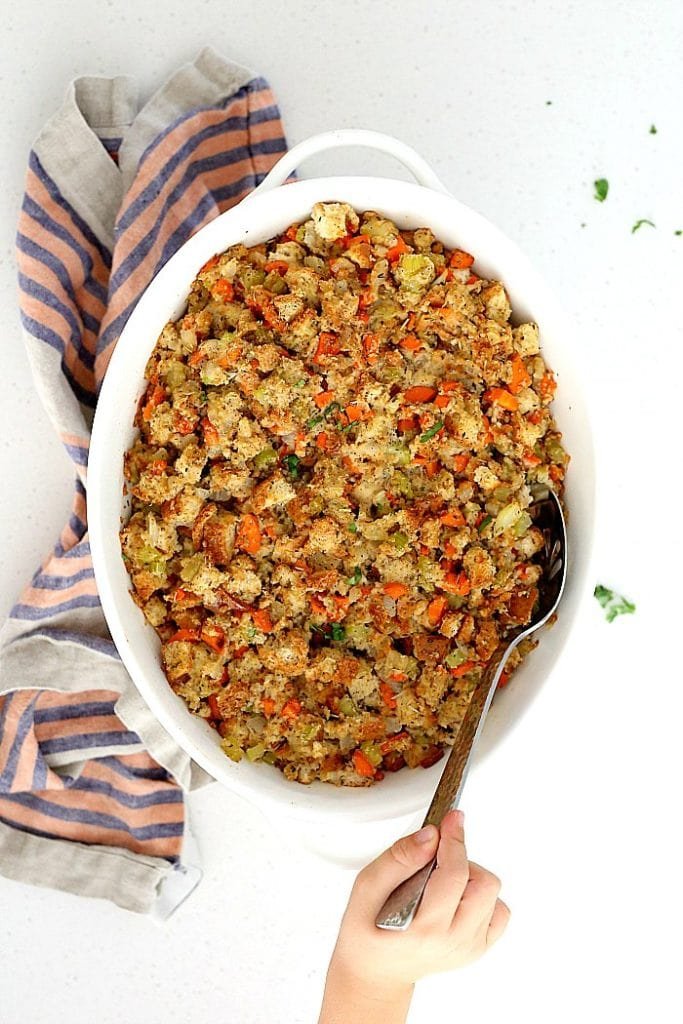 baked gluten free and vegan stuffing recipe made with celery, onion, carrots in a casserole dish with a serving spoon