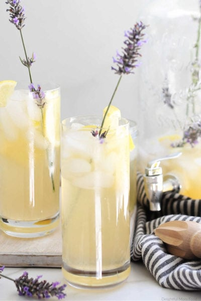 two glasses with lavender infused lemonade garnished with lavender stems and lemon slices