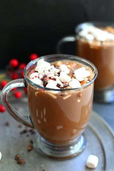 two mugs filled with the best vegan hot chocolate recipe topped with marshmallows, chocolate and peppermint bites