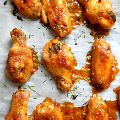 Get ready for the most tender gluten free sriracha chicken wings that fall off the bones! These baked party wings are dressed in a spicy sriracha sauce that will be the hit at the party! #sriracha #chicken #wings #party #superbowl #superbowlfood #tailgating #recipe #appetizer #glutenfree | Recipe at delightfulmomfood.com