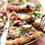 gluten free pizza with barbecue sauce on top, chicken and cilantro