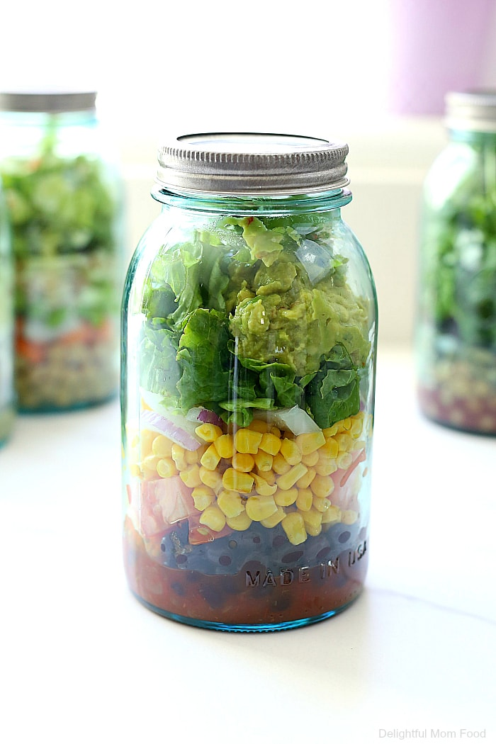 Meal prepping salads just got easier by layering them in mason jars. It keeps all the ingredients fresh but there is a trick to how to prepare it to stay fresh. Check out these 4 delicious meal prep ideas creating a salad in a jar! #mealprep #ideas #saladinajar #masonjarsalads #mealprepideas #glutenfree #healthy #recipes | Recipes at Delightful Mom Food