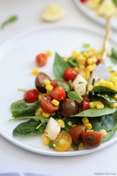 salad made with corn and tomatoes arugula basil and jicama in a light vinaigrette dressing served on a white platter