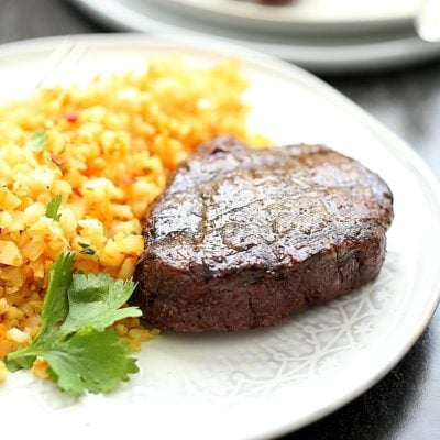 Tender top sirloin steak recipe with a buttery crisp exterior and rich juicy flavors. This hearty sirloin steak served with zesty cauliflower rice is a 30 minutes or less meal that is Paleo, Keto and Whole 30 friendly!  #whole30 #keto #paleo #30minutemeals #dinner #recipe #glutenfree #dairyfree #topsirloinsteak #steak #entree | Recipe at Delightful Mom Food