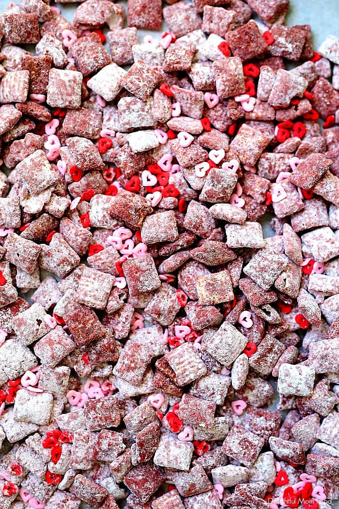 Fun and delicious pink muddy buddies (also known as puppy chow) are peanut butter, chocolate, butter, and powdered sugar coated Chex rice cereal colored with beet powder! These Valentine's muddy buddies are so simple for the kids to make and give as Valentine's Day treats to friends! #valentinesday #treats #dessert #glutenfree #quick #snack #puppychow #muddybuddies #recipe | Recipe at Delightful Mom Food