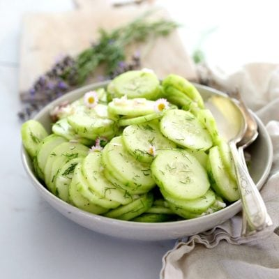 cucumber salad in a grey bowl served with serving spoons and lavender and dill in the background