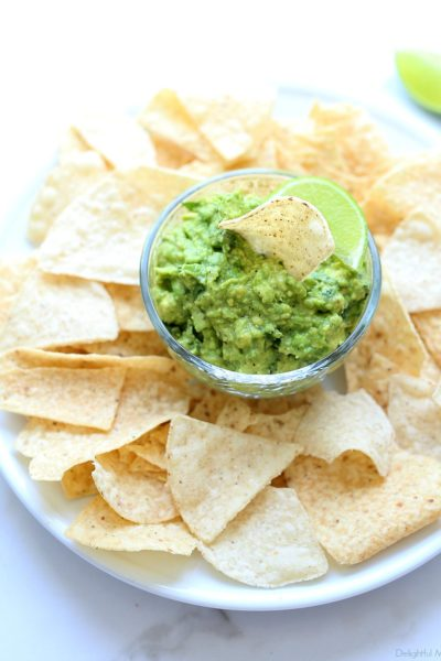 chunky guacamole recipe served on a plate with tortilla chips