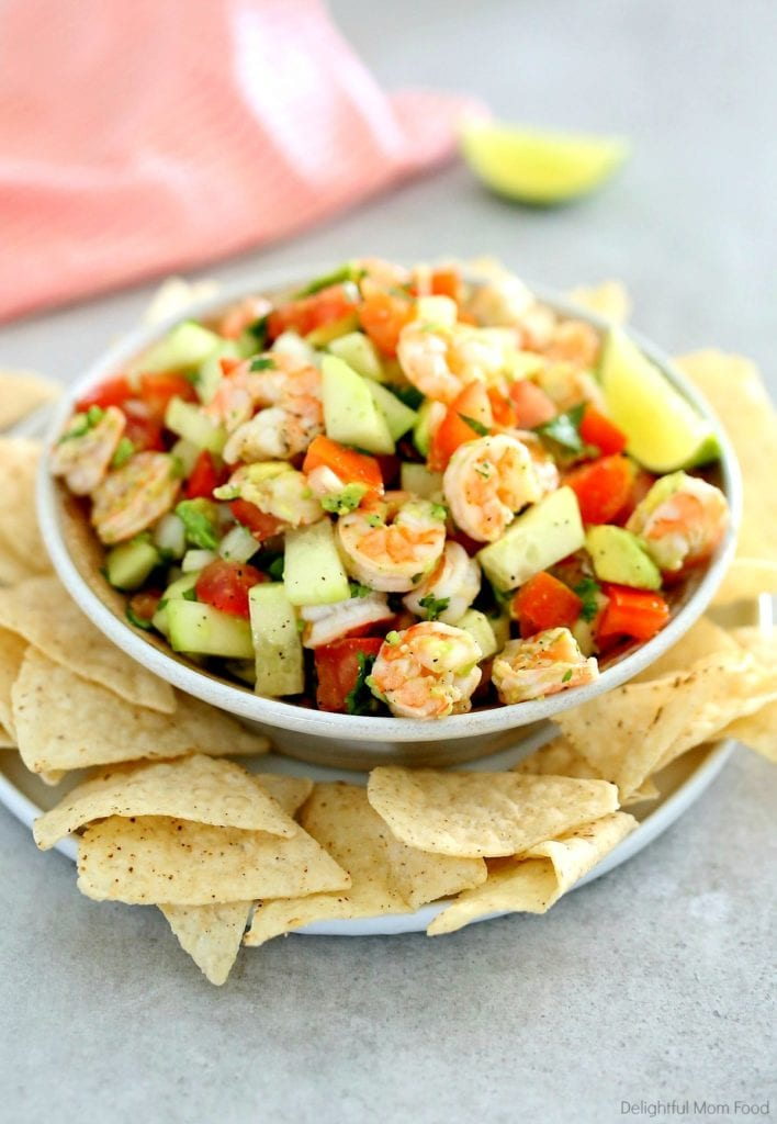 shrimp ceviche served in a bowl with chips and a peach dish towel