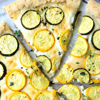 Slice of gluten-free zucchini pizza with a white cheese spread on a pizza pan