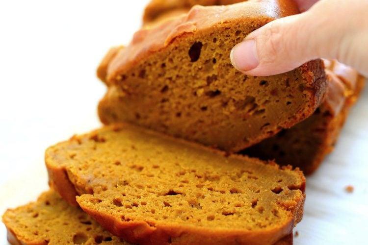 picking up slices of gluten free pumpkin bread