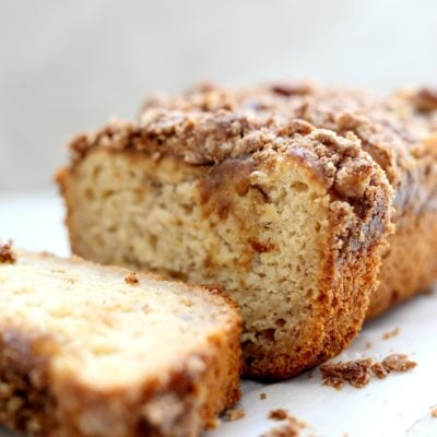 loaf of sliced gluten-free banana bread with a streusel topping