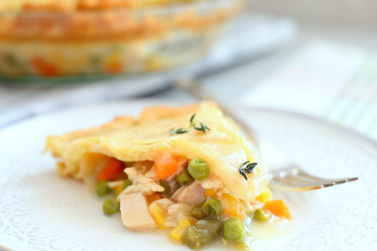 slice of gluten free chicken pot pie or turkey pot pie with fresh thyme on top and pie in the background