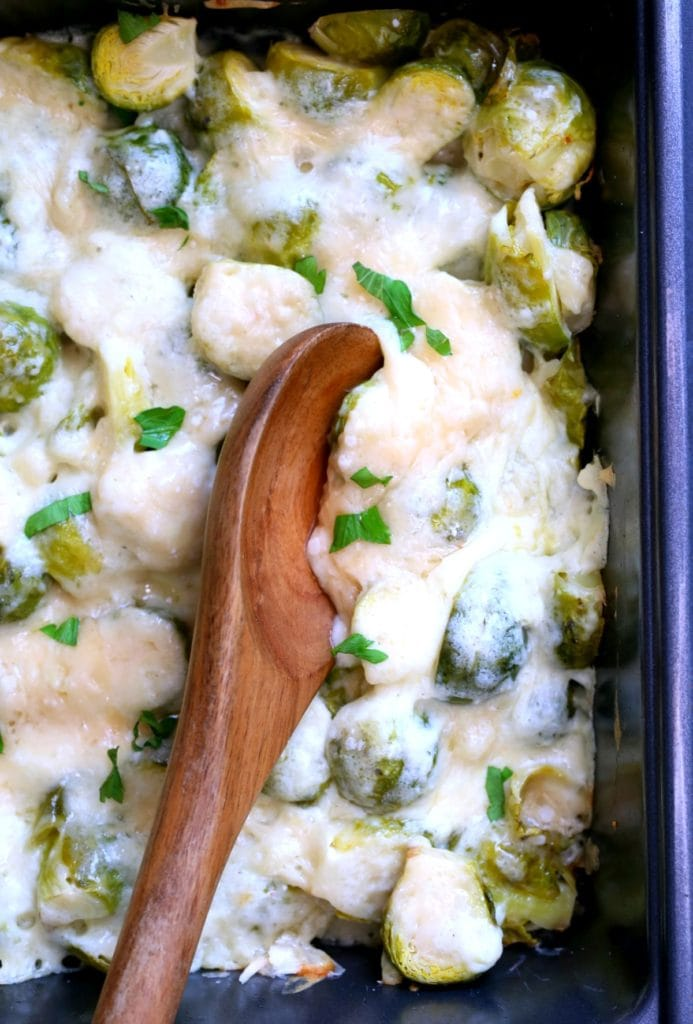 spoon in brussels sprouts gratin and parsley flakes on top