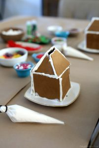 table with gingerbread house candy for decorations and a built house kit