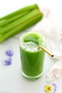 celery juice in a glass with a straw