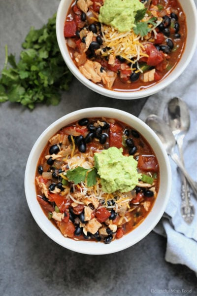 chicken chipotle chili in bowls with guacamole and cheese on top