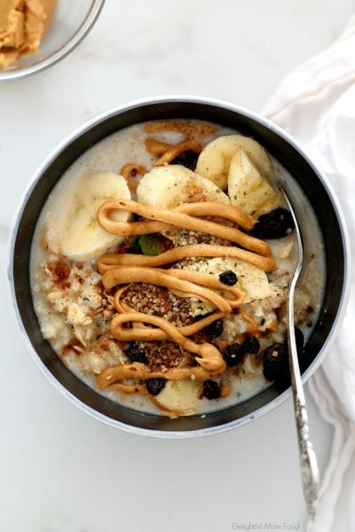 peanut butter drizzled on gluten-free oatmeal with banana slices, raisins and cinnamon