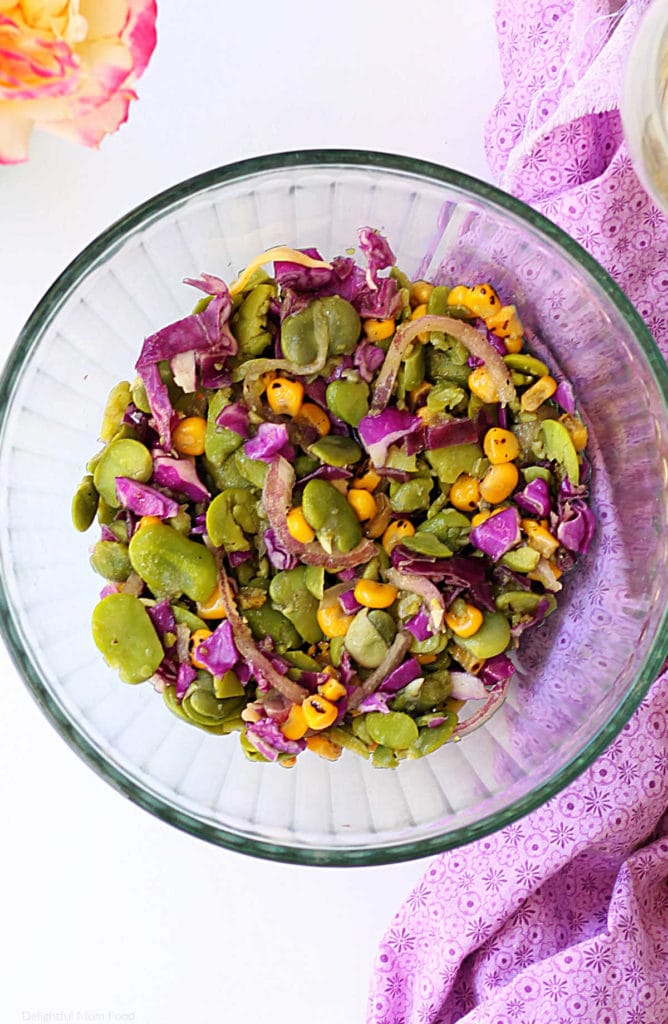 salad made of fava beans, corn, cabbage, onion in a glass bowl