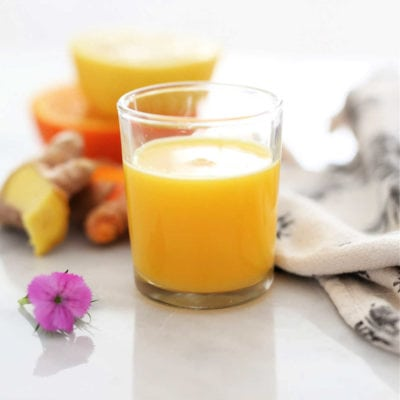 wellness ginger turmeric shot with lemon for cold in a shot glass