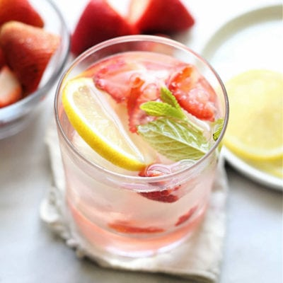 detoxing strawberry water for weight loss and clear skin infused with strawberries lemon and mint in a glass with ice