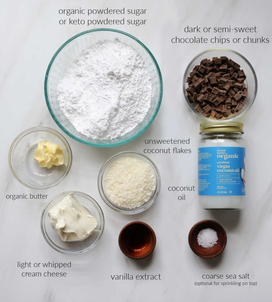 ingredients for making chocolate covered coconut balls using sugar-free powdered sugar, butter, cream cheese, coconut flakes, vanilla, chocolate, and coconut oil