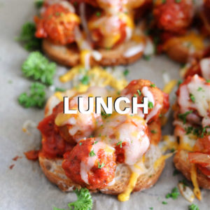 open faced meatball sandwiches on a parchment paper lined baking sheet