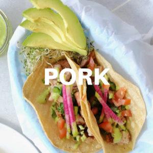 pork tacos with avocado sauce on a platter with avocado slices