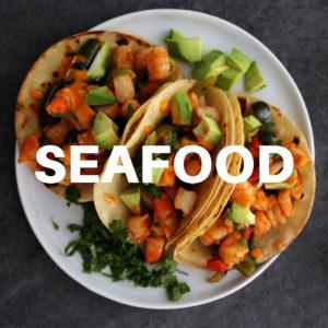 shrimp fajitas with diced avocado and sauce served a plate