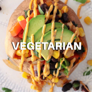 stuffed sweet potato with black beans corn tomato and avocado slices with southwest sauce drizzled on top