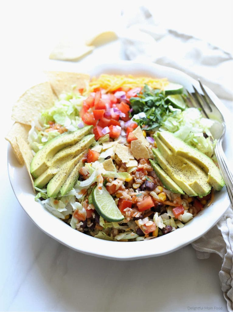vegetarian black bean taco salad in a bowl with serving spoon and fork