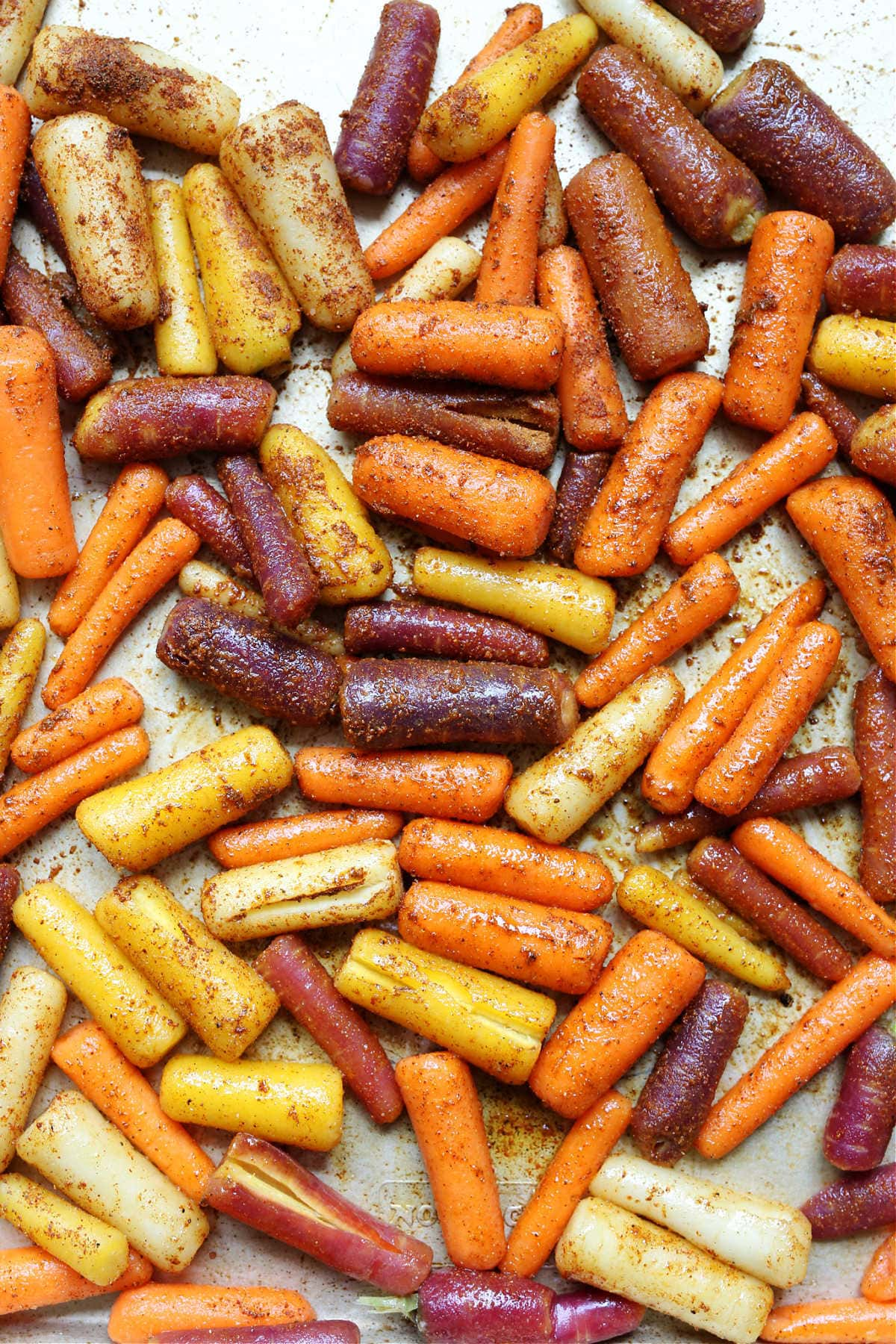 rainbow carrots seasoned and on a baking pan for roasting the vegetable