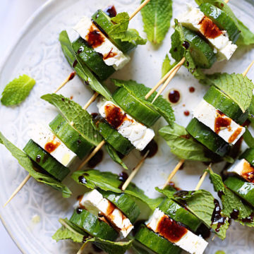 cucumber feta and herbs with balsamic drizzle served on toothpicks as an appetizer