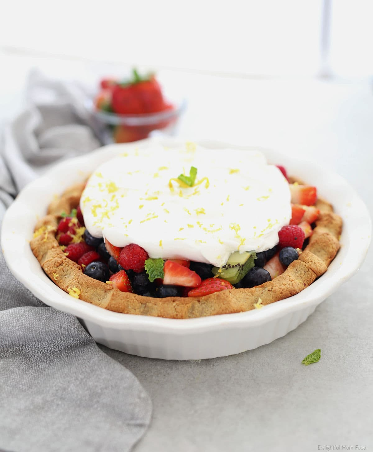 paleo pie filled with fresh fruit and whipped cream topping